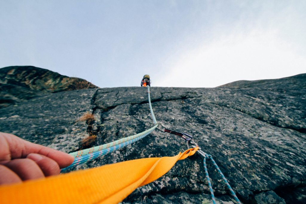 Looking up a rockface with a hand in the foreground grasping mountain climbing rope